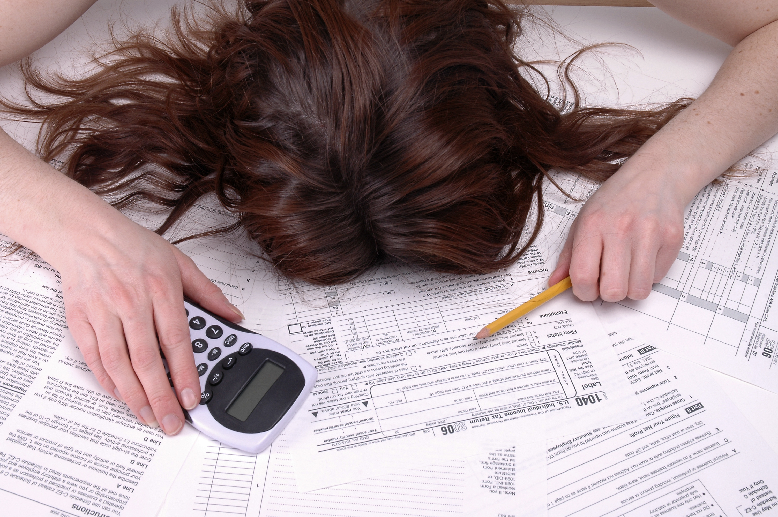 woman slumped over tax forms