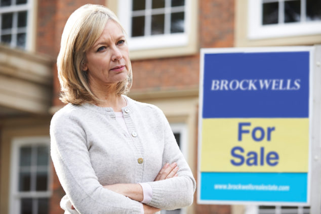 mature woman, arms folded, standing in front of For Sale sign