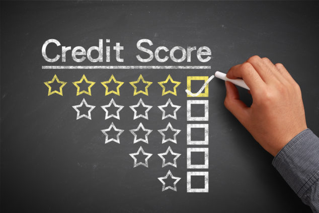 Hand with chalk is drawing credit score concept on the chalkboard, business credit rating concept