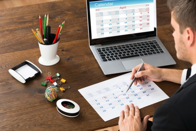 man at laptop with paper calendar, rota software concept