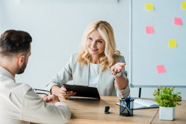 Woman and man talking in office, HR software concept