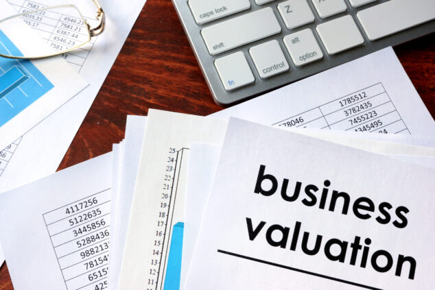Business valuation written on paper, laptop keyboard, private company valuation concept