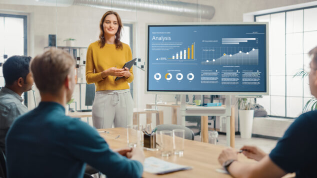Woman stands in front of PowerPoint presentation presenting growth analysis, investing in a start-up concept
