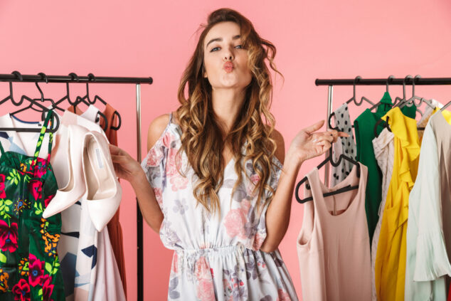 Trendy young woman holding up clothes, Deals of the Week concept