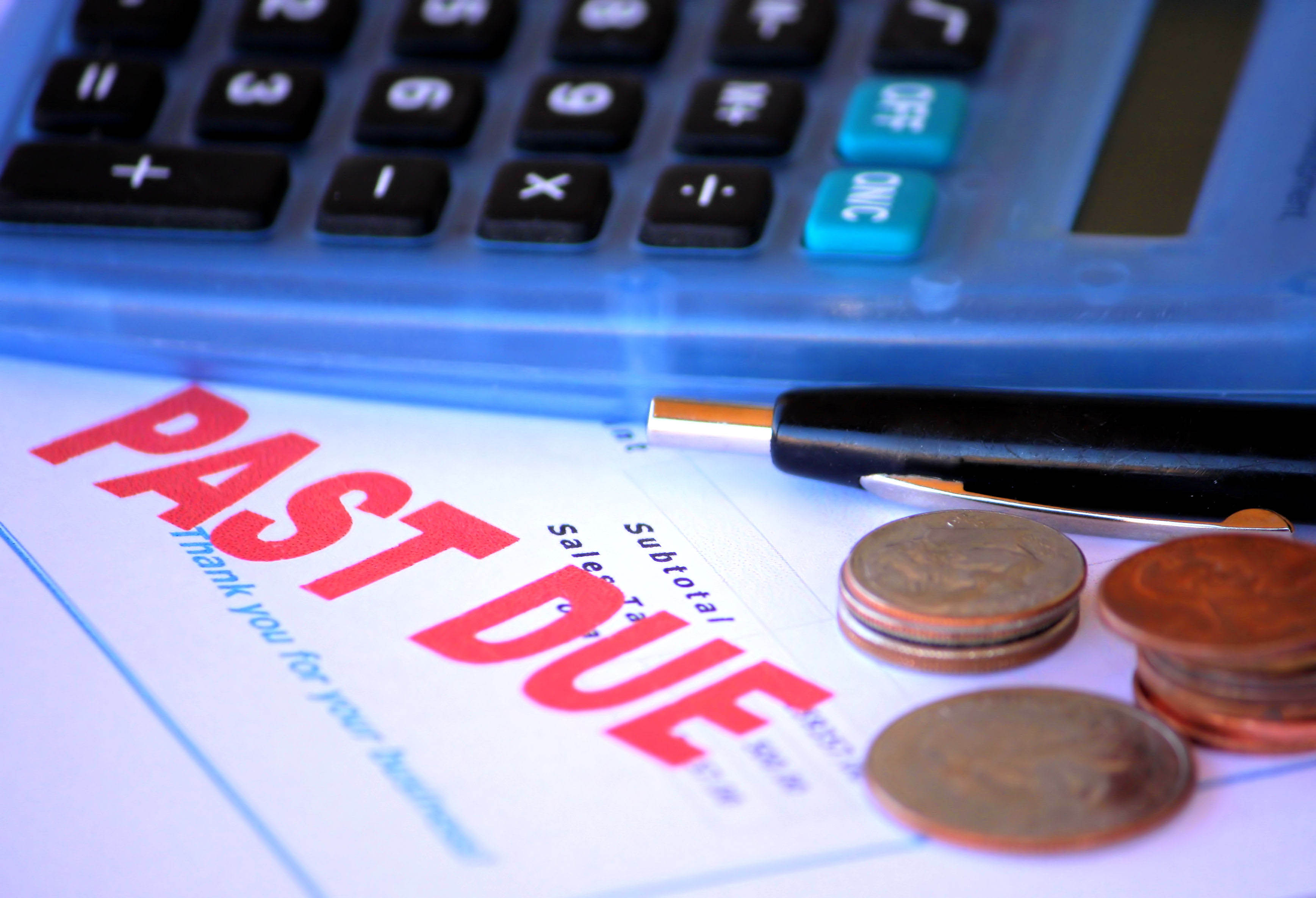 Past Due stamped on letter beside calculator, debt recovery concept