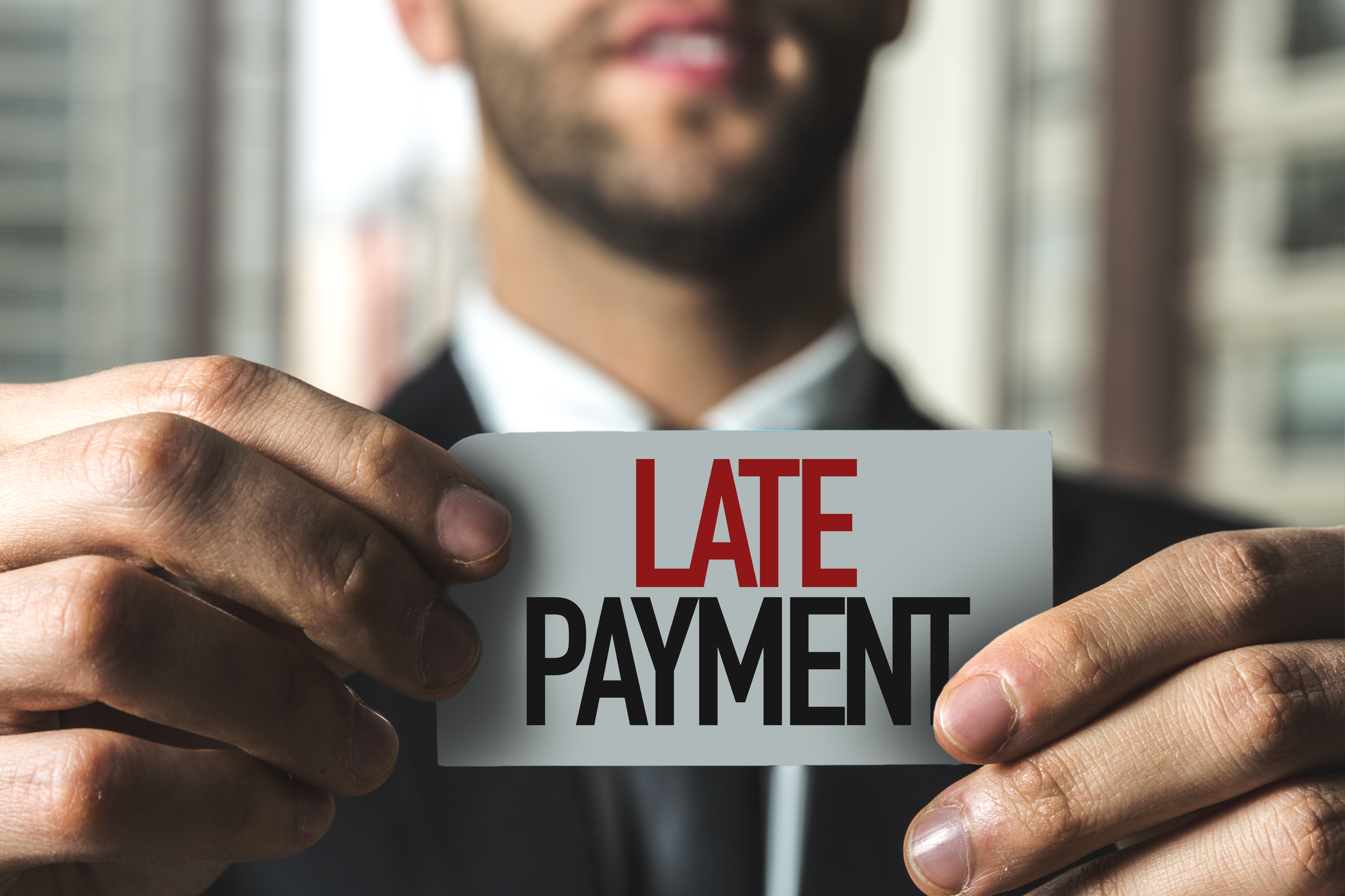man holding late payment sign