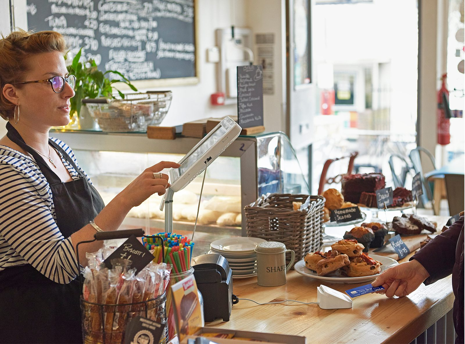 Female cafe owner taking Square card payment