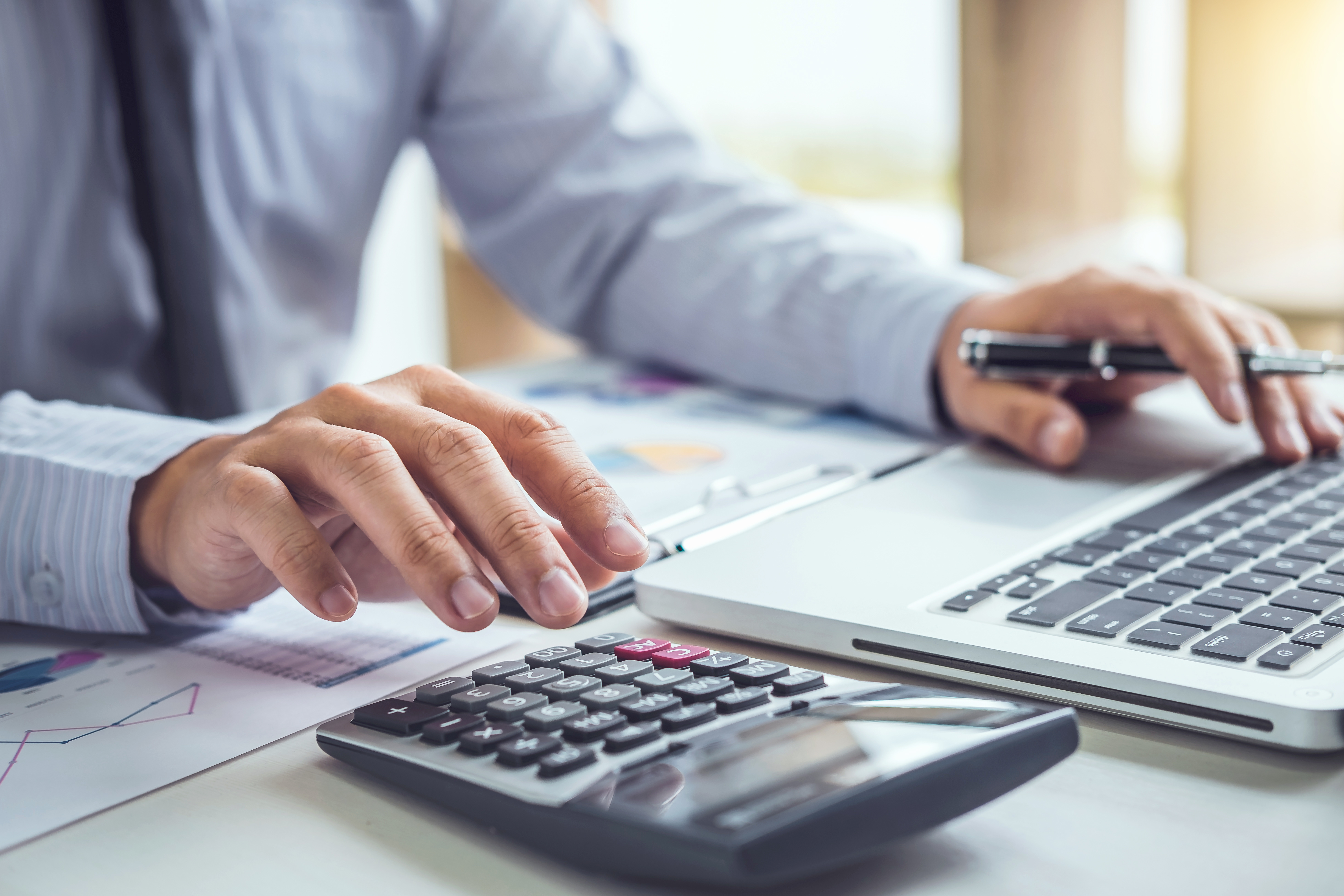 Man operating calculator to illustrate piece on benefits of SEIS/EIS