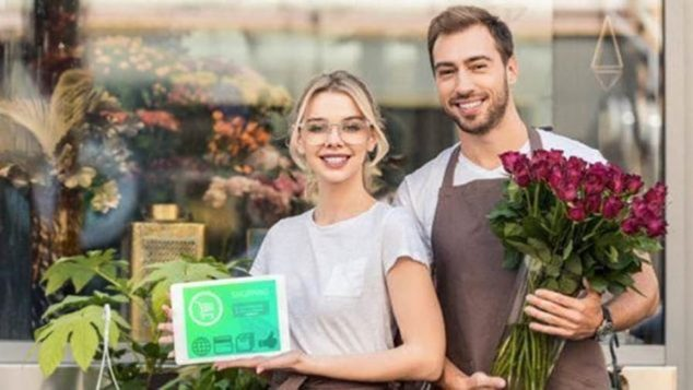 smiling couple; man holding flowers and woman showing off laptop