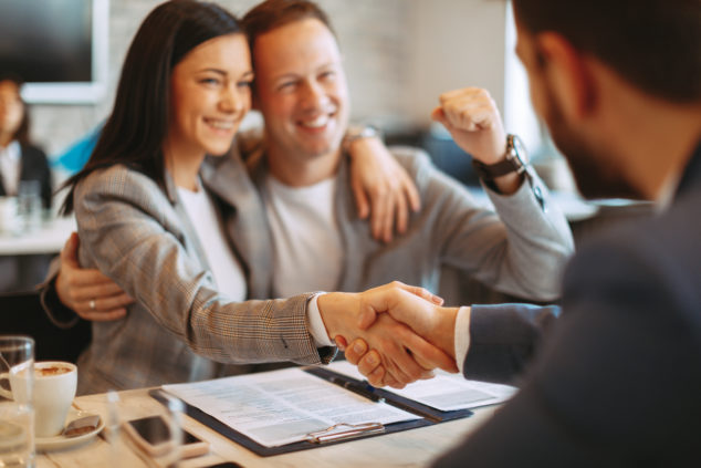 Young business couple make a deal and shake hands business loan concept
