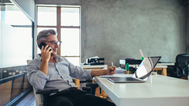 Businessman in office talking on phone. cloud telephony concept