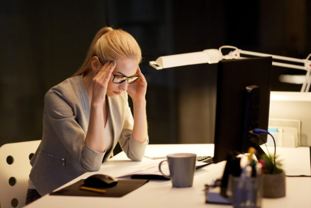 Anxious woman sitting alone at desk at night, Brexit uncertainty concept