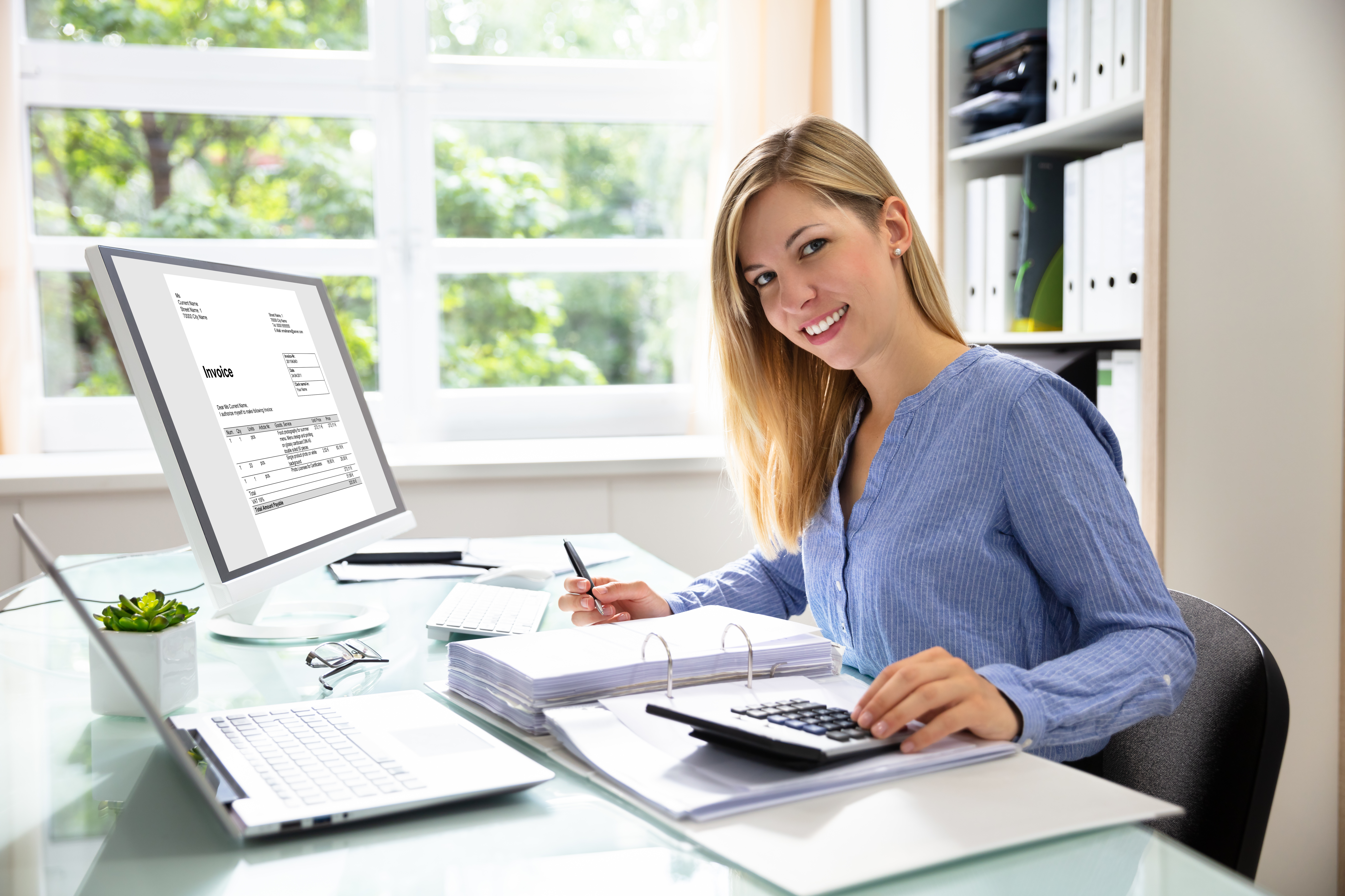 Young Businesswoman Calculating Bill With Computer And Laptop On Desk, UK small buisiness accountancy software concept