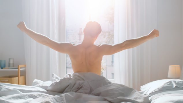 Man stretching getting out of bed, morning routine concept