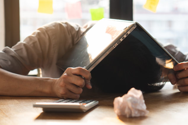 Man with head inside laptop, worst startup ideas concept