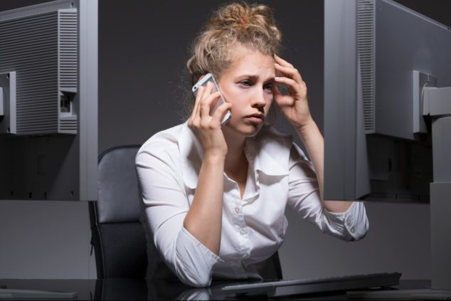 Tired and depressed woman at her workplace, hustle-and-grind concept