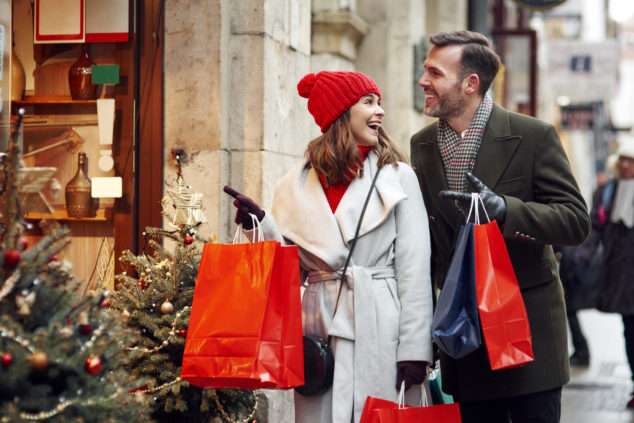 Couple Christmas shopping, woman pointing at shop window, small retailers Christmas concept