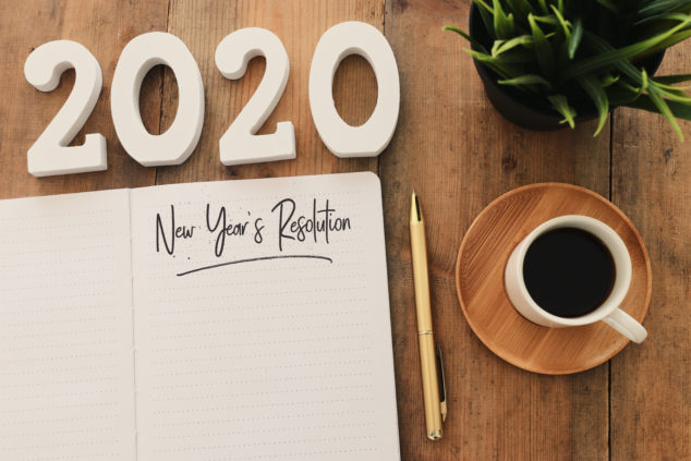 Business concept of top view 2020 year's resolution list with notebook, cup of coffee over wooden desk, SEO tips 2020 concept