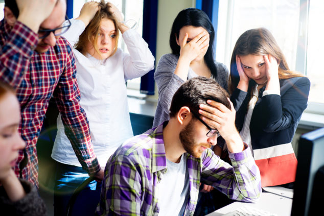 Young people clutch their heads standing over bearded colleague who's made a mistake, start-up mistakes concept