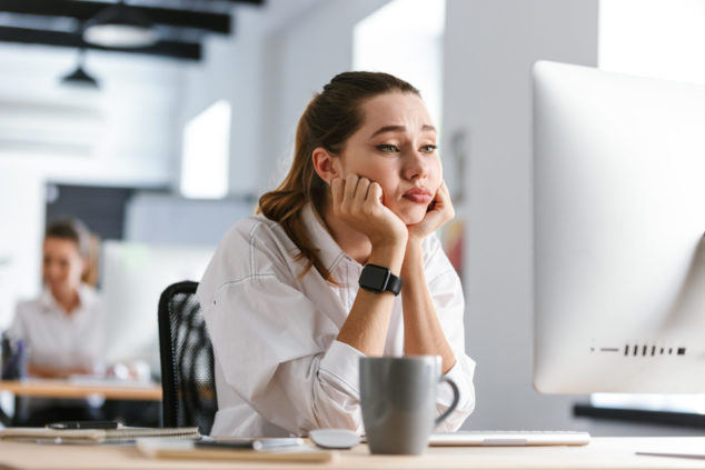 Bored young woman dressed in shirt sitting at her workplace, escaping the nine to five concept