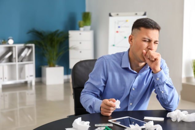 Young man ill with flu in office, coronavirus statutory sick pay concept