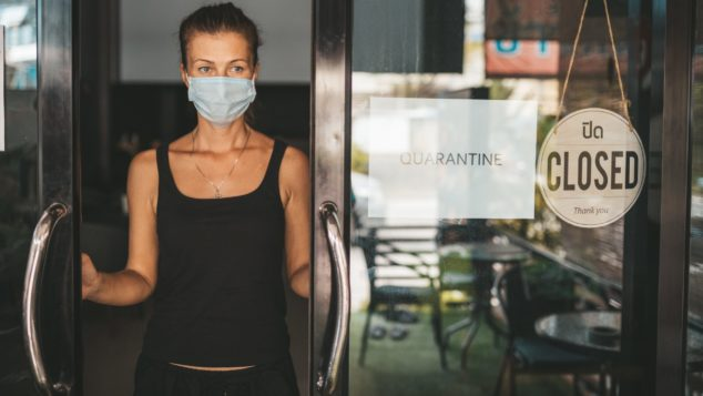 Shop owner in facemask standing at partially open shop doorway, part-time furlough concept