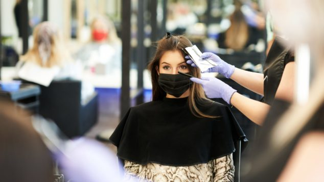 Woman having hair coloured in hairdressers wearing facemask, reopen hairdressers concept