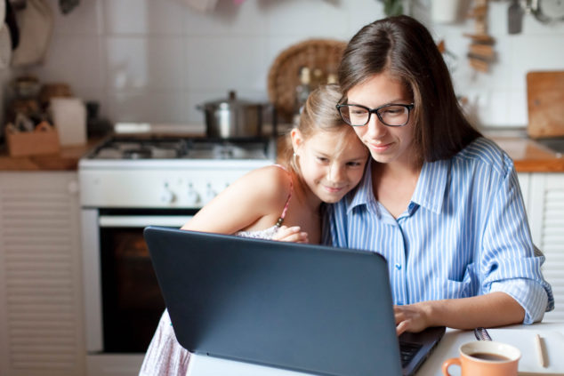 Mother working on laptop hugging daughter, single parents concept