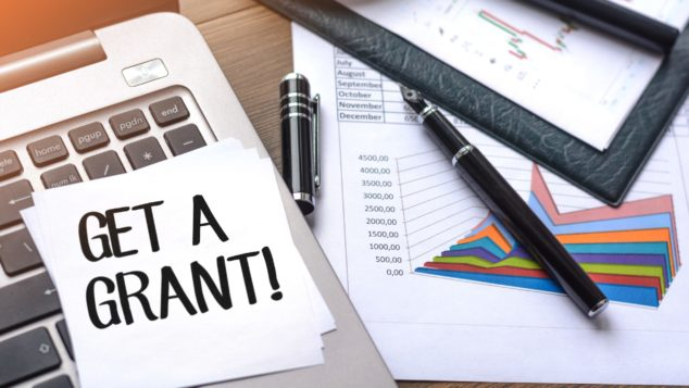'Get a Grant!' note on top of calculator, small business technology grant concept