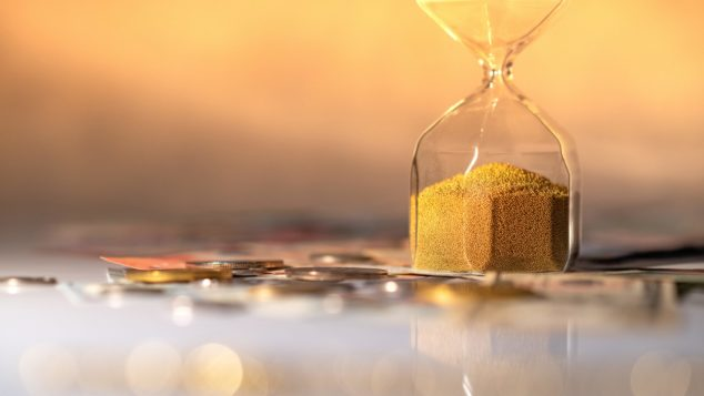 Reflection of hourglass running out of time on glowing table with currency. Bounce Back Loan concept