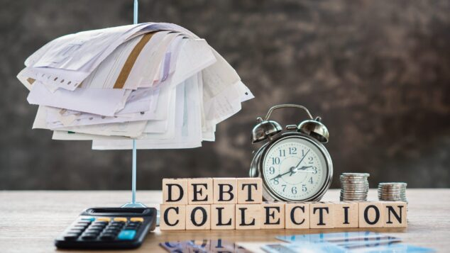 Alarm clock with bill spike and Debt Collection sign, Bounce Back Loans debt concept