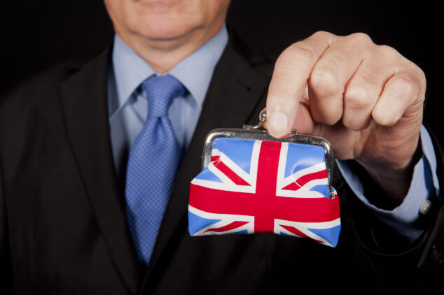 Businessman holding Union Jack purse, self-employed tax concept