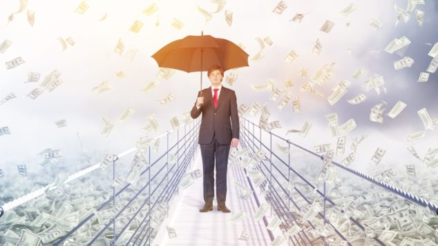 Businessman standing on bridge being rained on by money holdiing umbrella, bridging finance concept