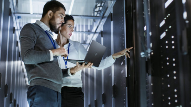 IT workers inspecting server rack, digital adoption concept