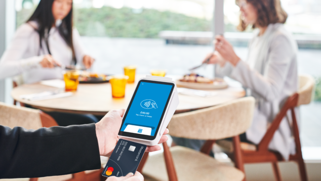 Hand using Square card reader with women having lunch in background, contactless concept