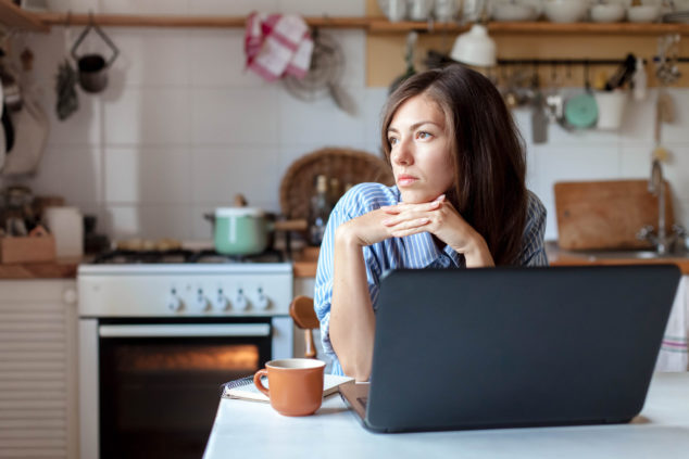 Woman working at kitchen table looking wistful, excluded self-employed concept