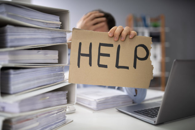 Office worker hemmed in by files holding up help sign, emergency Covid-19 help concept