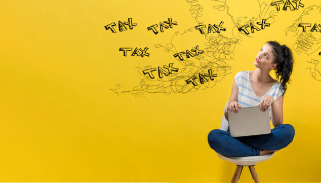 Young woman pondering word tax written on yellow wall, Making Tax Digital concept