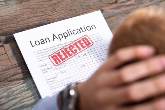 Disbelieving man with head in hands and rejected loan application form, Recovery Loan Scheme concept
