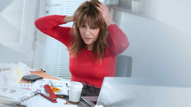 Stressed businesswoman in red dress in messy office, digital space concept